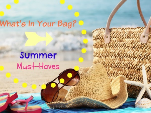 Summer beach bag with straw hat,towel,sunglasses and flip flops on sandy beach
